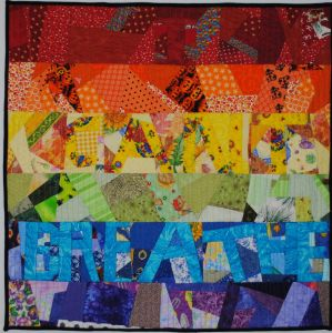 "Words ""I can't breathe"" embedded in rainbow stripes of crazy patchwork"