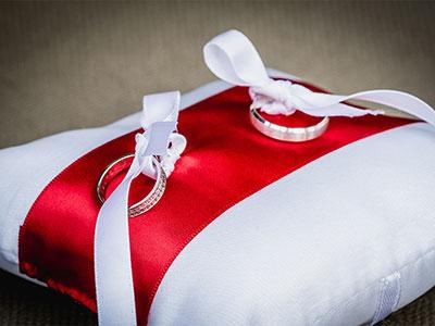 photo de détail alliances mariage sur coussin rouge et blanc