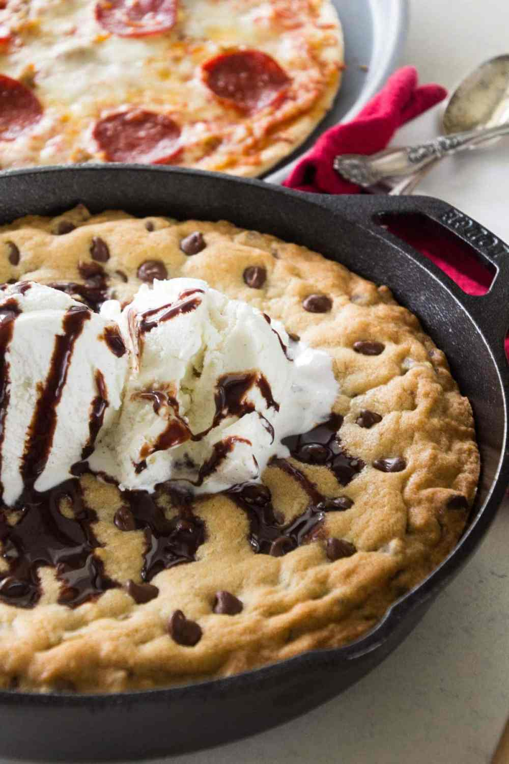 An amazing Chocolate Chip Skillet Cookie topped with ice cream and chocolate drizzle.
