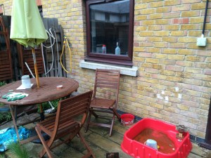 Patio, house wall with window to rear of photo. Wooden table and chairs, with parasol, in front left of photo. Small red plastic paddling pool front right.
