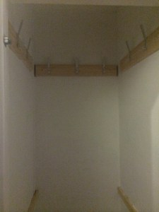 Inside of tall narrow white cupboard, showing coat hooks.