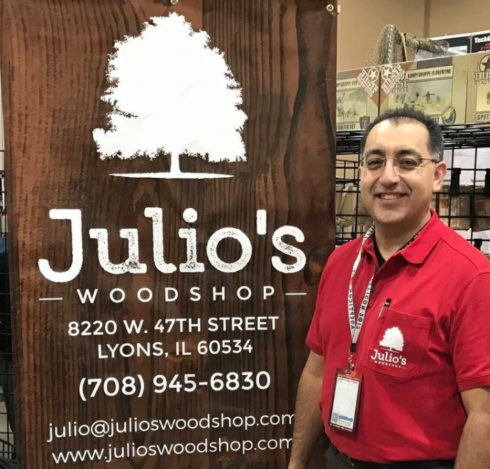 """Man in red shirt standing by sign that says """"Juilo's Woodshop"""""""