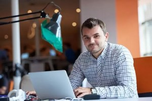 Мъж се усмихва седи с лаптоп