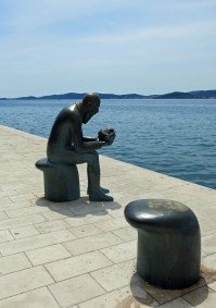 Bronze Man with Shell on the quay.