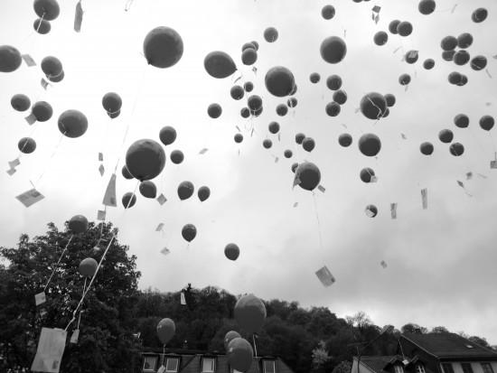 Hier ein Bild von in den Himmel aufsteigenden Luftballons bei einem Luftballonwettbewerb