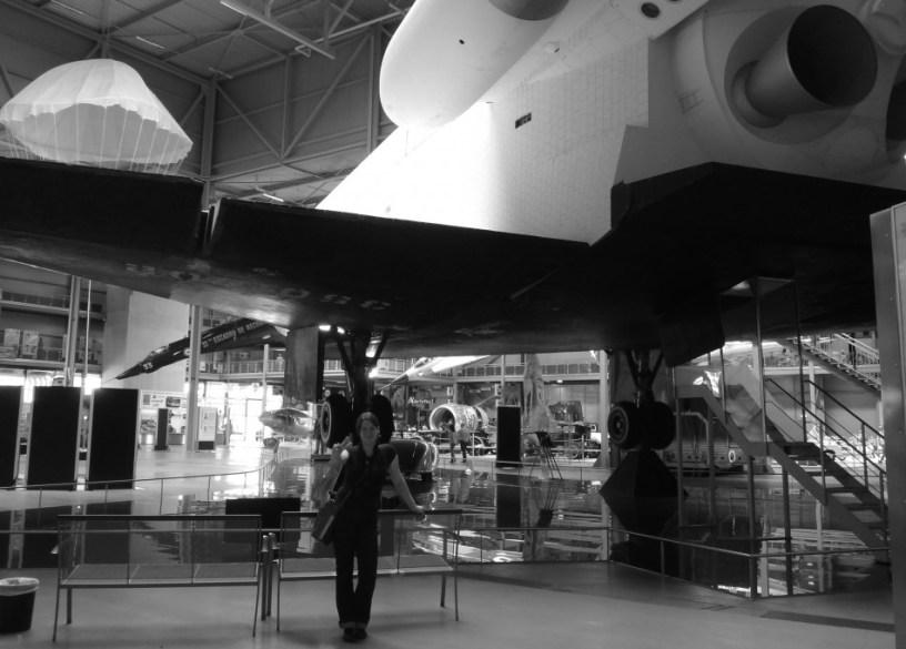 Hier ist eine junge, gutaussehende Frau vor dem in Speyer ausgestellten Space Shuttle zu sehen. Dass die Frau gut aussieht, ist eine objektive Einschätzung und hat rein gar nichts damit zu tun, dass es sich dabei um mich selbst handelt.