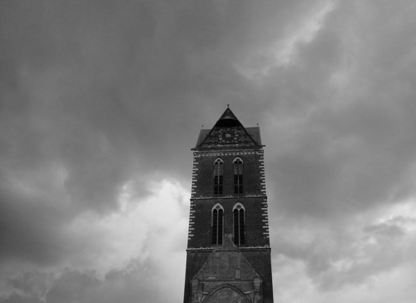 Hier ist der Turm einer Kirche in Wismar zu sehen, vor einem sehr bewölkten Himmel