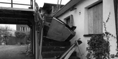 """Hier ist ein Bild von einem heruntergekommenen Haus mit einer Freitreppe aufs Dach zu sehen. Die Absperrung mit einem """"Zutritt verboten"""" Schild ist eingetreten."""