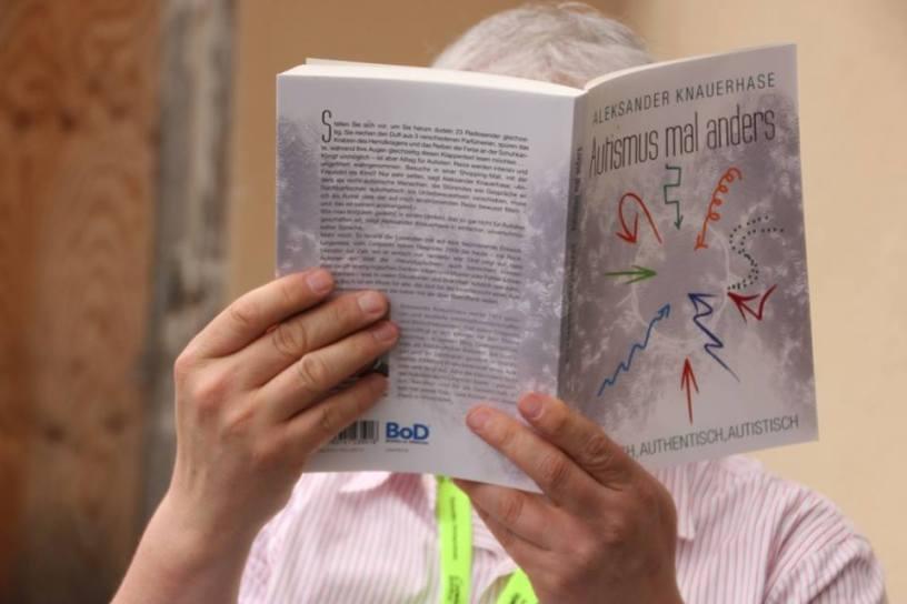 Hier ist der Buchrücken von Aleksanders Buch zu sehen. Ein Leser auf dem Literaturcamp hält es so, dass sein Gesicht dahinter verschwindet. Der Redaktion ist natürlich bekannt, um wen genau es sich handelt. Ha, ha.