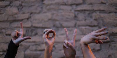 """Hier ist ein Bild von vier Frauenhänden zu sehen, die zusammen das Wort """"Love"""" bilden."""