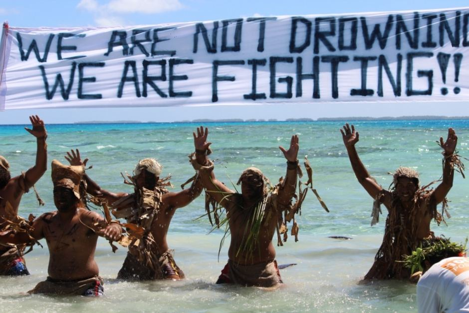 """Protesters in Fiji show strength in the face of rising sea levels with the 350 Pacific slogan – """"We are not drowning, we are fighting."""""""