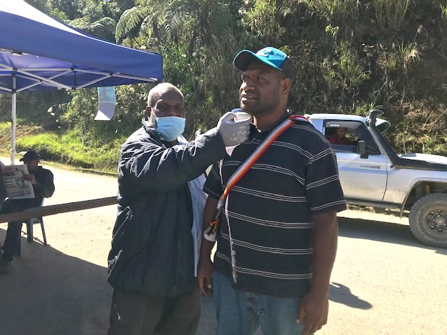 CARE security guard Bonnie Opiyafo has his temperature checked at a police checkpoint along the Highlands Highway at the border of the Eastern Highlands Province. Supplied: Justine McMahon
