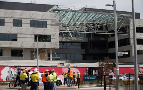 Workers gather outside the construction site where the glass roof collapsed.
