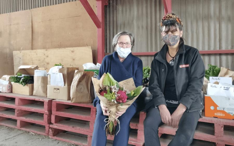Shirley Saywell (right) rewards regular customer Linda Bennett with some complimentary flowers. Photo: Juliette Milbank