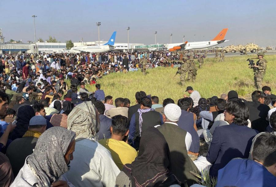 afghanistan people sitting at an airport guarded by military