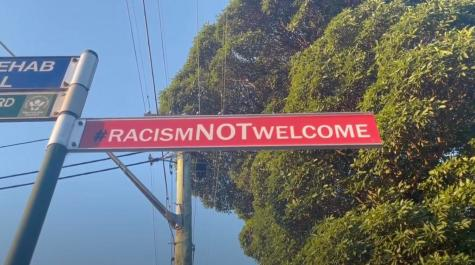 street sign saying racism not welcome