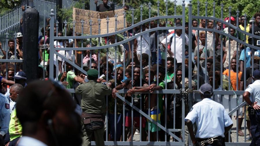 protestors locked behind a guarded gate
