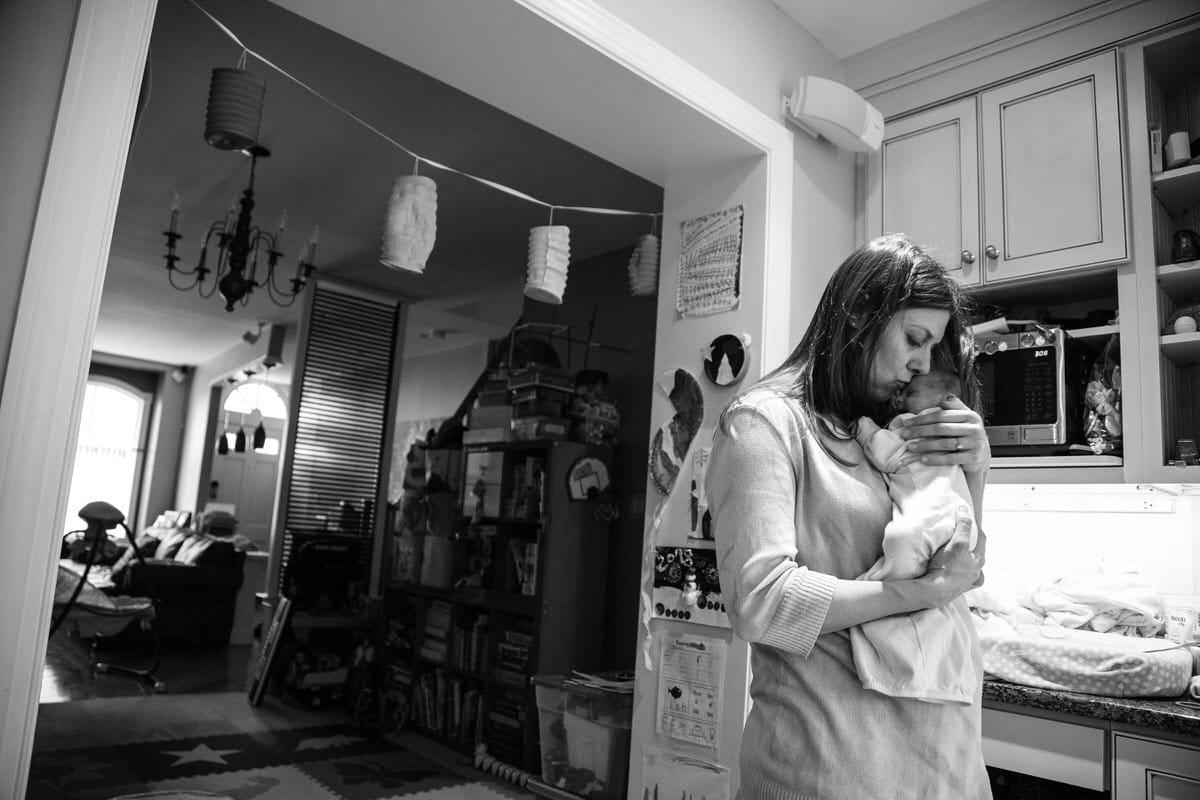 Mother holding newborn baby in kitchen.
