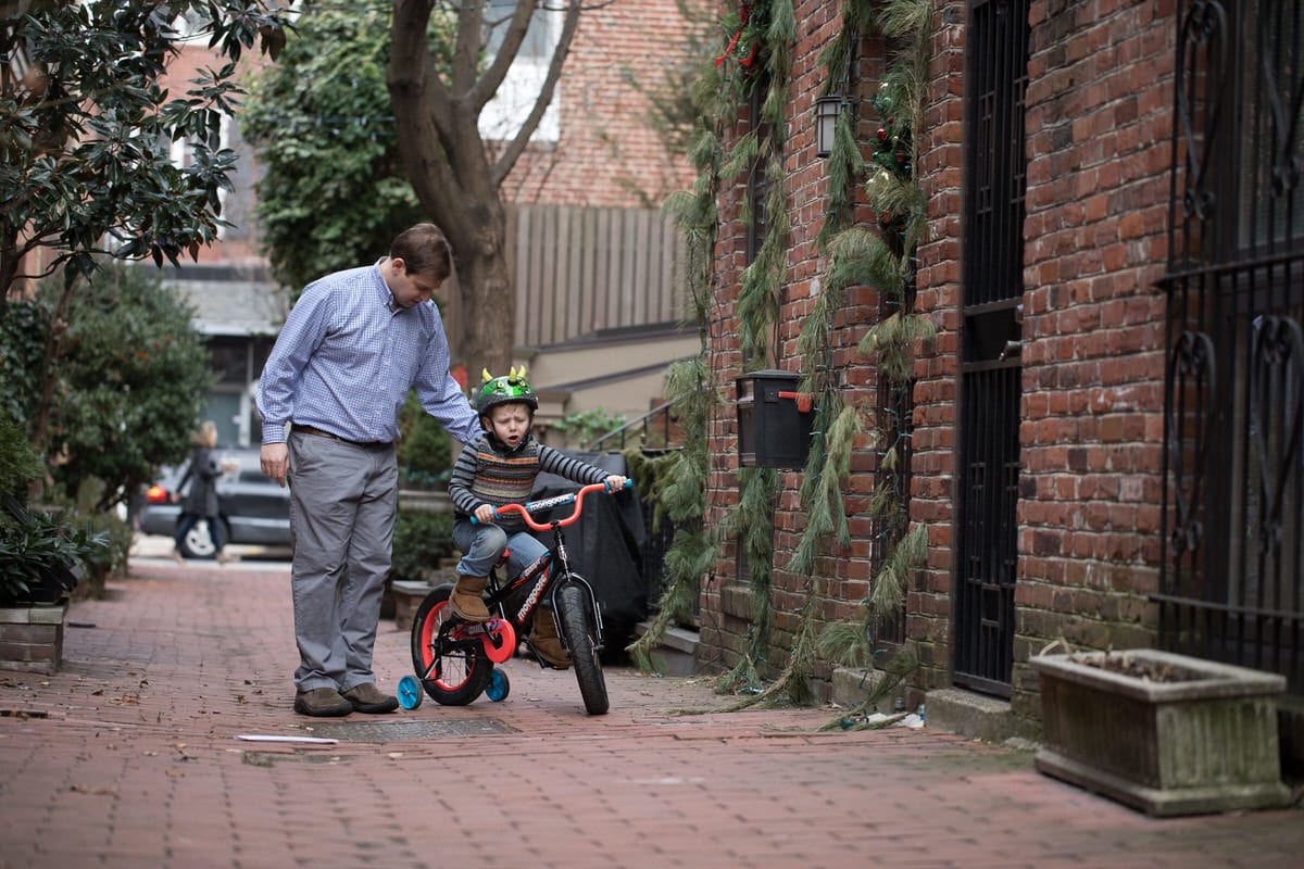 Father helping son ride a bike in Old City Philadelphia.