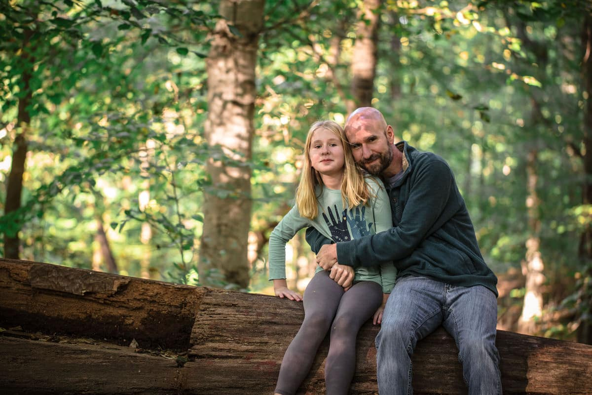 Father and daughter sitting on log together.