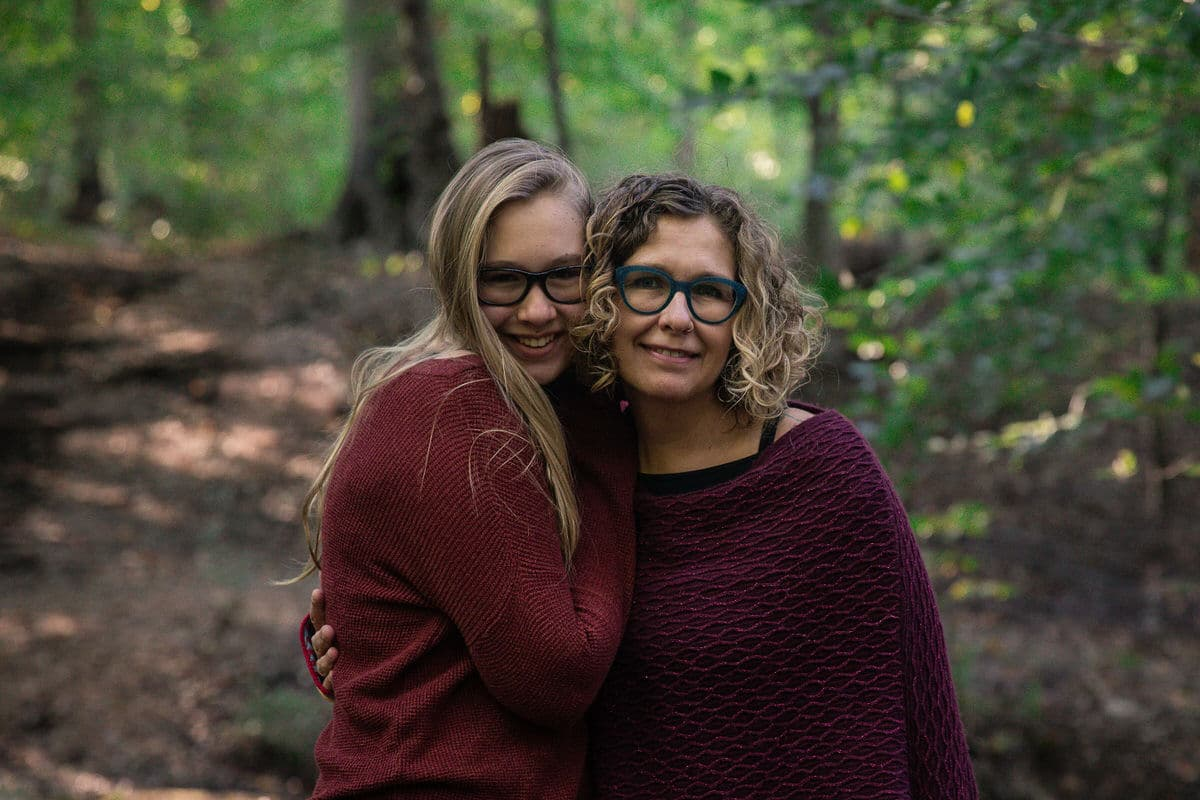 Mother and daughter hug with wooded background.