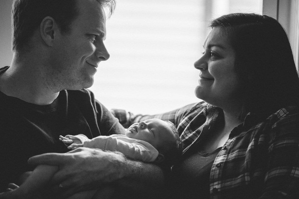 New parents smiling at each other over baby.