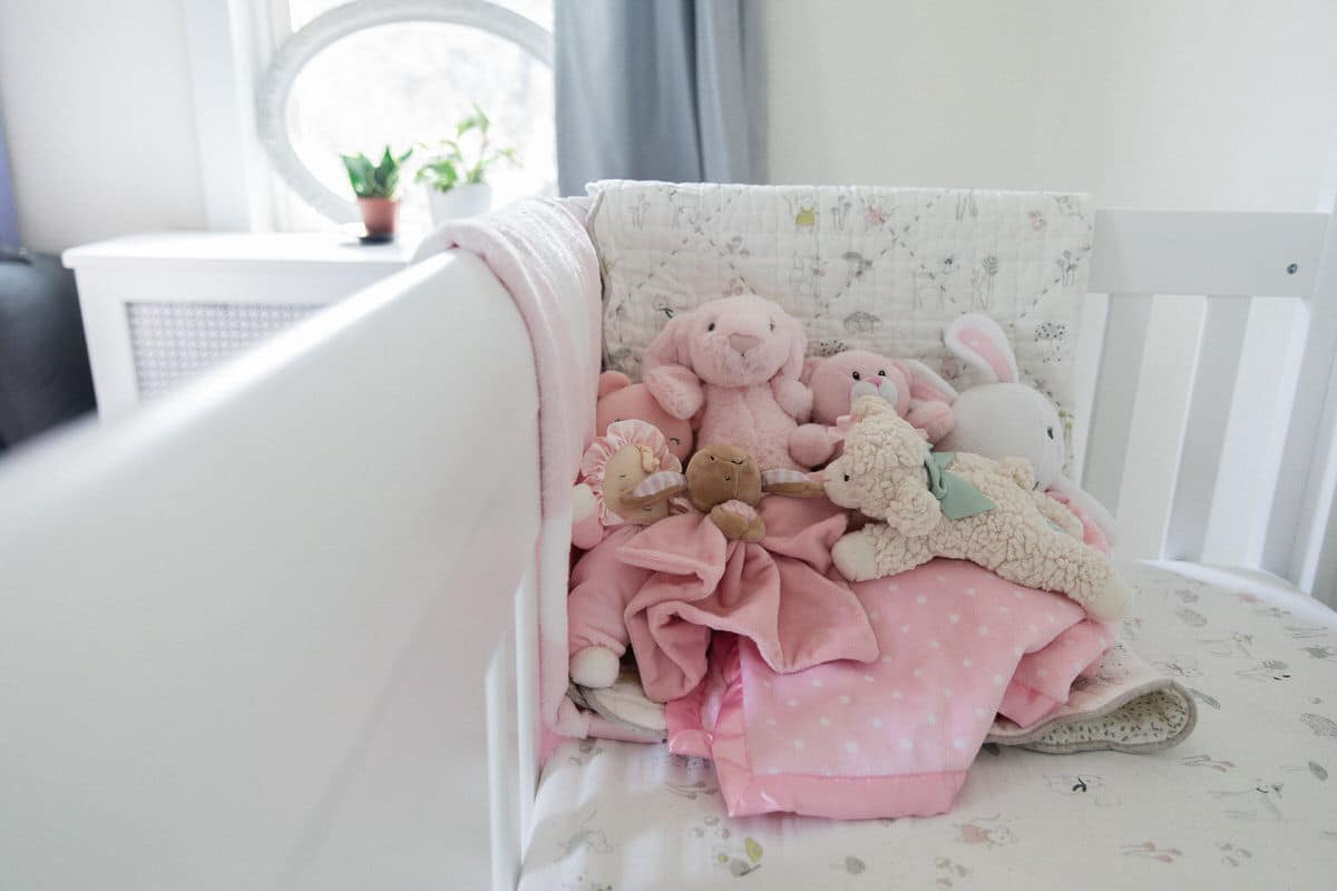 Blankets and stuffed animals in baby's crib.