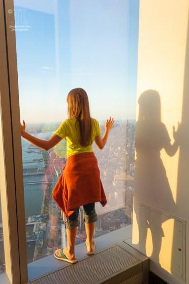 Meine große Tochter lehnt sich gegen eines der großen Fenster des One World Trade Center. http://junghahn24.com/finale-in-new-york/