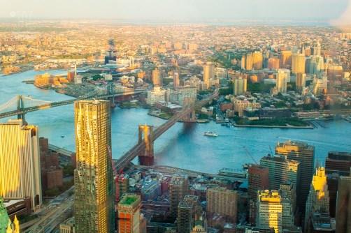Der Schatten des One World Trade Center legt sich wie ein Zeiger über die Stadt. Blickrichtung Osten sieht man den Eastriver, Brooklyn Bridge und die Manhattan Bridge.