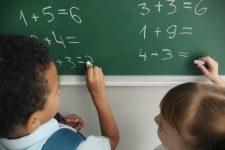 Schoolchildren writing on chalkboard in classroom during math lesson