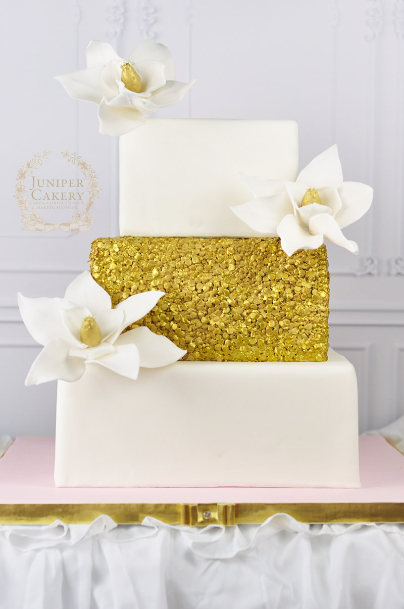 Gilded sequin and magnolia flower wedding cake by Juniper Cakery