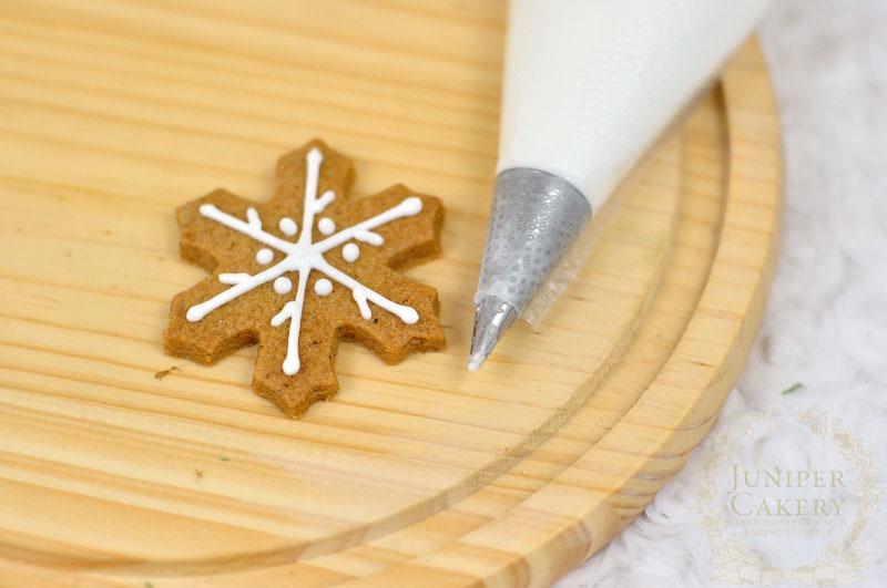 Piping snowflake cookies by Juniper Cakery