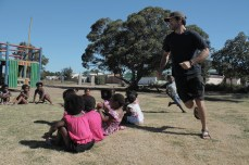 Nick plays duck-duck-goose with preschool kids while leading a physical education session.