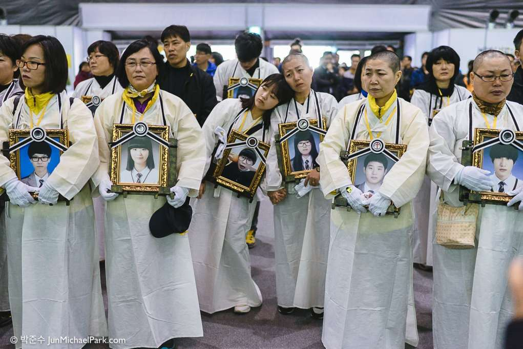 April 2015, just a few weeks before the 1st anniversary, the government proposes the enforcement decree of the Sewol law, which undermines the very independence of the investigative committee. The Sewol families are outraged. Some 70 parents shave their heads in protest, and about 150 parents embark on a 2-day walk protest wearing mourning white dress and holding their children's funerary portraits. A victim's mother and sister lean on each other just before the march began.