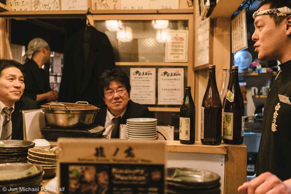KAGOSHIMA, JAPAN - February 4, 2016: Customers exchange banters with the owner and enjoy Japanese food and drinks at an izakaya in Kagomma Furusato Yataimura. The place is a mock village of food stalls and small restaurants. Its quaint alleyways with colorful lanterns provide a glimpse into authentic Japanese dining experience.