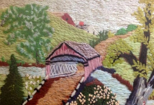 A scene of embroidered yarn of a covered bridge going over a river.