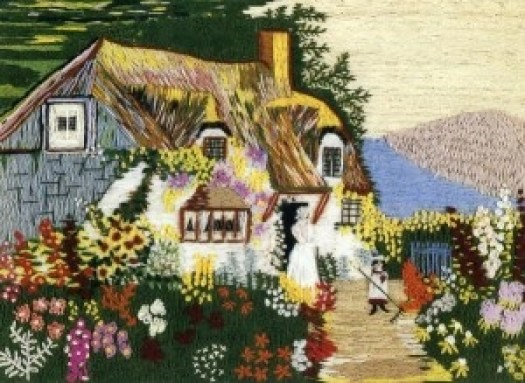 An embroidered yarn scene of a cottage with flowers in the garden in the foreground and a path on which a little girl walks on the right side of the picture.