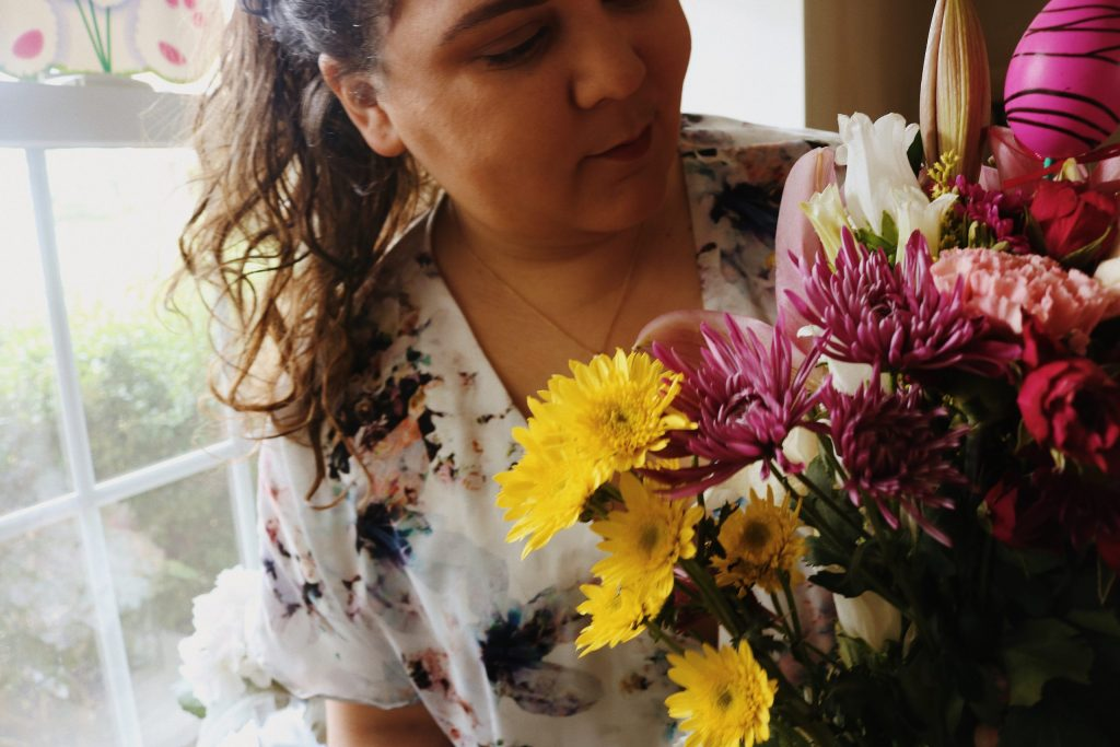 a photo of me smiling at a bouquet of flowers with an Easter egg decoration within them.
