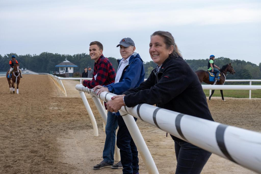 Racing partners watch their horse's morning track workout by the rail on the side of the dirt track.