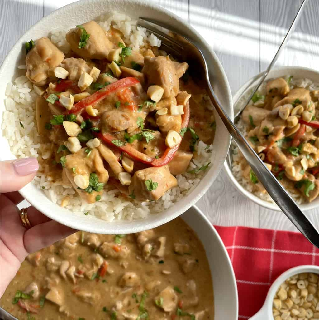 hand holding a bowl of satay chicken slow cooked served over rice