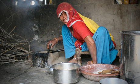 An Indian woman cooking in an outhouse in the village of Parsurampura