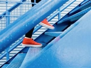person wearing orange sneakers walking up blue stairs
