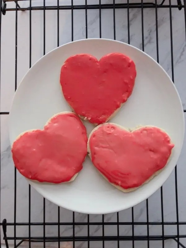 Heart shaped cookies with red icing on a white plate
