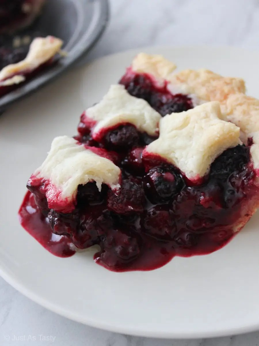 Slice of blackberry pie on a white plate
