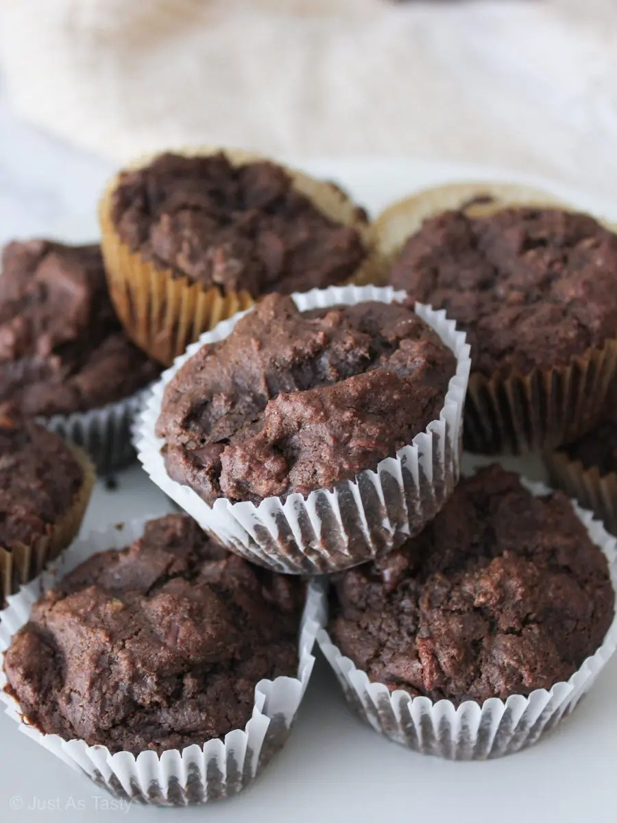 Gluten free chocolate muffins piled on a marble surface.