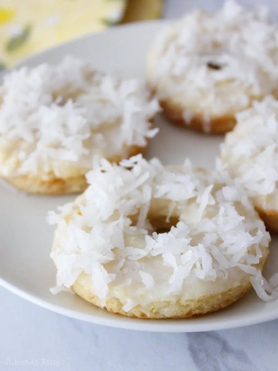 Donuts topped with coconut flakes on a white plate