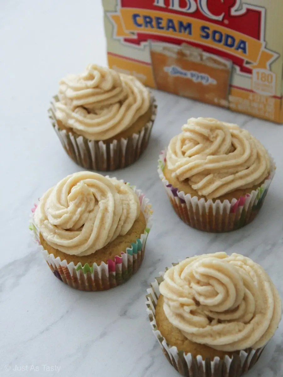 Cream soda cupcakes with swirl frosting on a white marble surface.