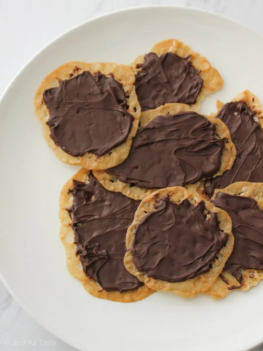 Pile of chocolate covered lace cookies on a white plate