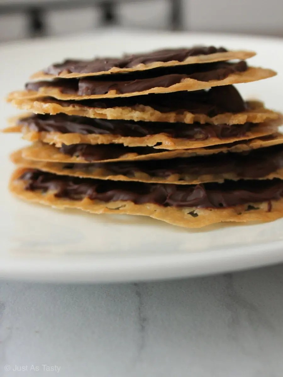 Stack of thin lace cookies on a white plate