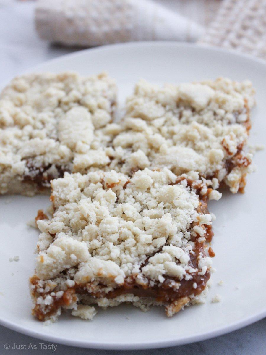 Three caramel crumble bars on a white plate